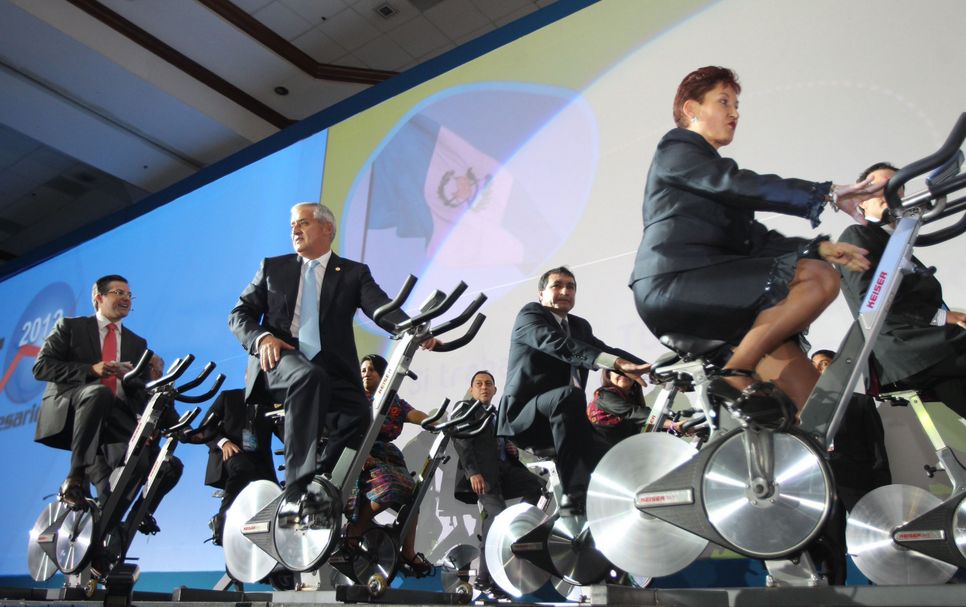 Why is the President of Guatemala Riding a Bike on Stage in a Suit?