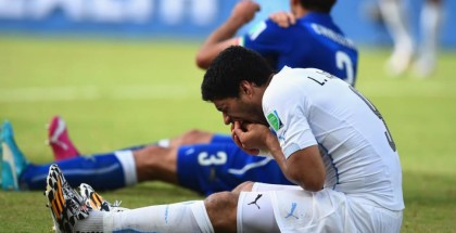 Luis Suarez reacts in pain after he appears to bite Italy's Guirgui Chiellini